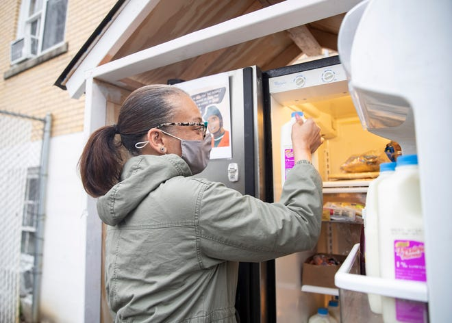 LJ Abraham, founder of 901 Community Fridges, places a carton of milk in the first community fridge at First Congregational Church in Memphis, Tenn., on Thursday, March 11, 2021.