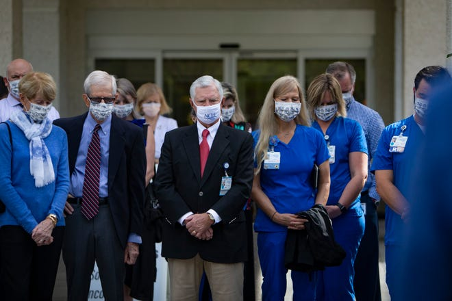 NCH Hospital staff and community members bow their heads in prayer during a ceremony to commemorate the one-year anniversary of the hospital admitting its first patient at the start of the pandemic, Thursday, March 11, 2021, at NCH Baker in downtown Naples.