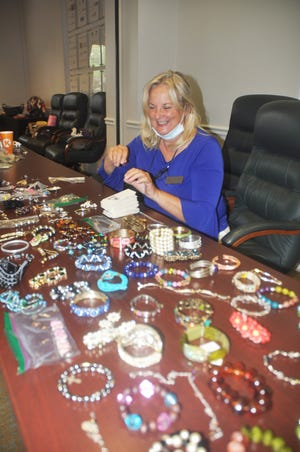 Olivia Woods sorts the bracelets at The Hub at SWFL Inc. (formerly the Bonita Springs Chamber of Commerce) in Bonita. Woods is a member of the Zonta Club that collected more than 1,000 pieces of jewelry that will be given to Bonita Springs Elementary School so students can give them as gifts to their mothers on Mother's Day.