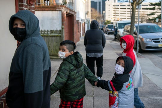 Yessina Moreno walks with her children Sebastian Moreno, 9, from left, Daniel Moreno, 6, Isabel Moreno, 3, and Omar Moreno, 8, outside their home in Atlantic City, N.J. on Thursday, March 11, 2021.