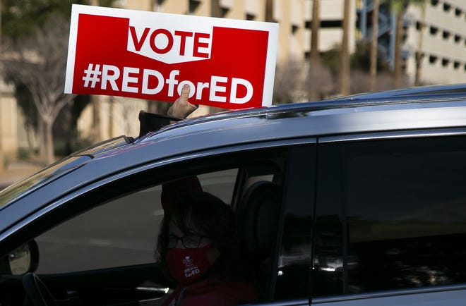 Supporters of Proposition 208 drive around the Arizona Capitol in Phoenix on March 10, 2021.
