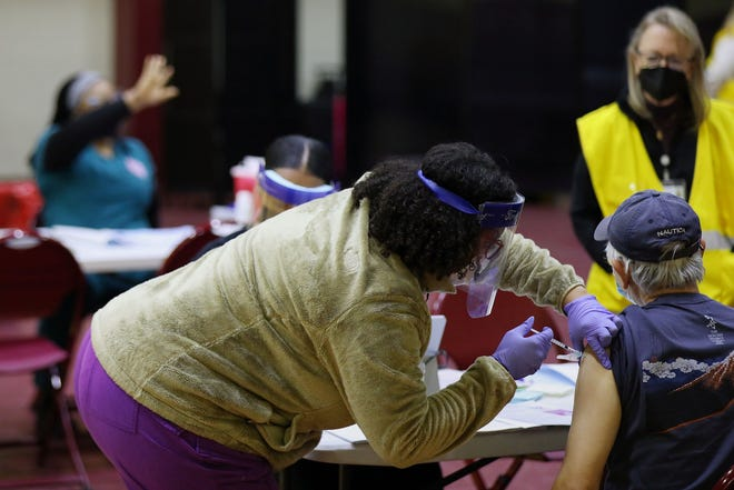 A health care worker vaccinates a man at a community COVID-19 vaccination clinic run by the Philadelphia Department of Public Health at University of the Sciences' Bobby Morgan Arena in West Philadelphia on Feb. 27, 2021. (Tim Tai/The Philadelphia Inquirer/TNS)