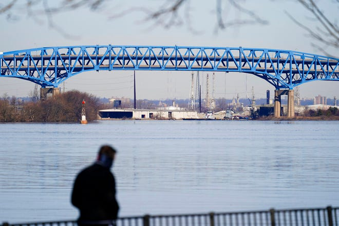 A person walks past the Interstate-95′s mile-long double-decked Girard Point Bridge in Philadelphia, Wednesday, Feb. 24, 2021. PennDOT named several bridges including the Girard Point Bridge that it said it is considering tolling to pay for the reconstruction. (AP Photo/Matt Rourke)