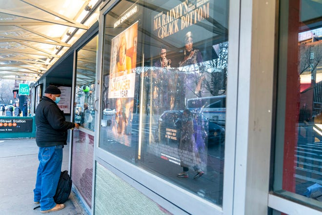 "Charlton Ruddock purchases a ticket for ""MLK/FBI"" at the box office of the IFC Center, Friday, March 5, 2021, in New York. After growing cobwebs for nearly a year, movie theaters in New York City reopen Friday, returning film titles to Manhattan marquees that had for the last 12 months read messages like ""Wear a mask"" and ""We'll be back soon."" Cinemas in the city are currently operating at only 25% capacity, with a maximum of 50 per each auditorium. (AP Photo/Mary Altaffer)"