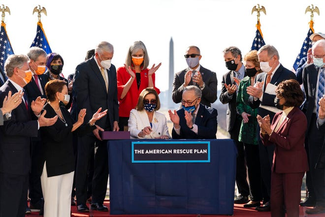 House Speaker Nancy Pelosi and Senate Majority Leader Chuck Schumer celebrate after signing the $1.9 trillion COVID-19 relief bill during a ceremony on Capitol Hill on Wednesday. President Joe Biden signed the measure on Thursday.