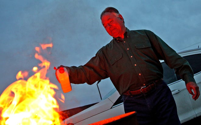 Bill Bartosh drops lighter fluid into a barrel containing burning face masks during an event sponsored by the San Angelo Republican Women held at the VFW on Wednesday, March 10, 2021.