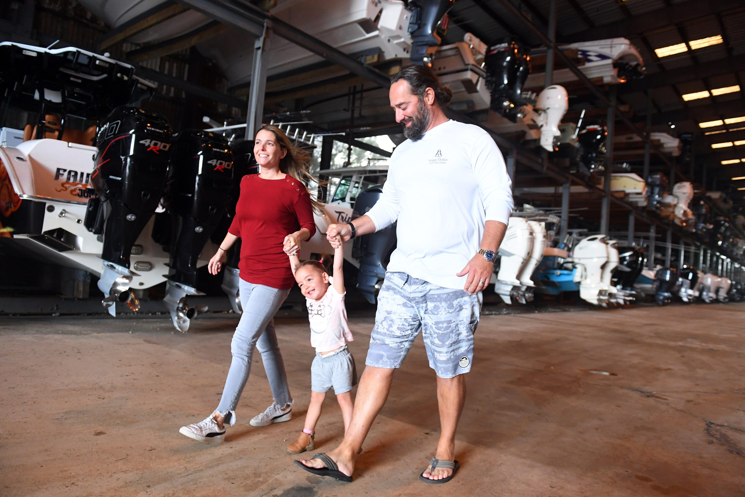 Jenny and Austin Cameron, of Austin, Texas, walk with their daughter Coltie, 2, through the stacks of boats in dry dock at Meridian Marina, on Tuesday, March 9, 2021, in Palm City. The Camerons are the new owners of the marina and are preparing for extensive repairs to the existing storage facility, adding additional storage, boat sales, a repair shop and a waterfront restaurant.