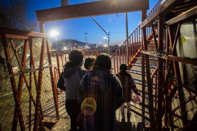Children and women cross a pedestrian bridge in Juarez, Mexico, on March 11, 2021 after being returned to Mexico from the U.S.