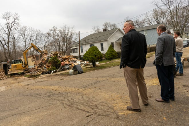 Zanesville police detectives John McElhaney and Phil Michel watch as the source of many drug cases was destroyed on Bates Street Thursday morning.