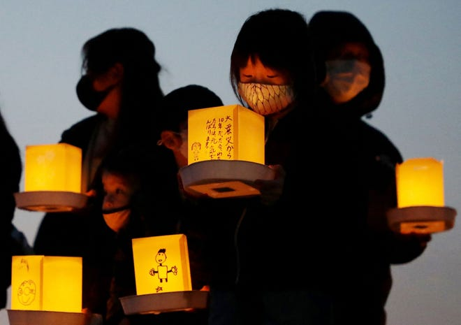 Local residents hold lanterns with messages for earthquake and tsunami victims in Yamada, Iwate prefecture on March 11, 2021.