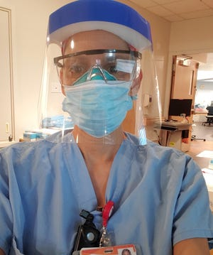 Nurse Celia Nieto, 44, poses for a photo while wearing two masks, safety glasses and a face shield, while on duty at the Las Vegas-area hospital she works at caring for COVID-19 patients.