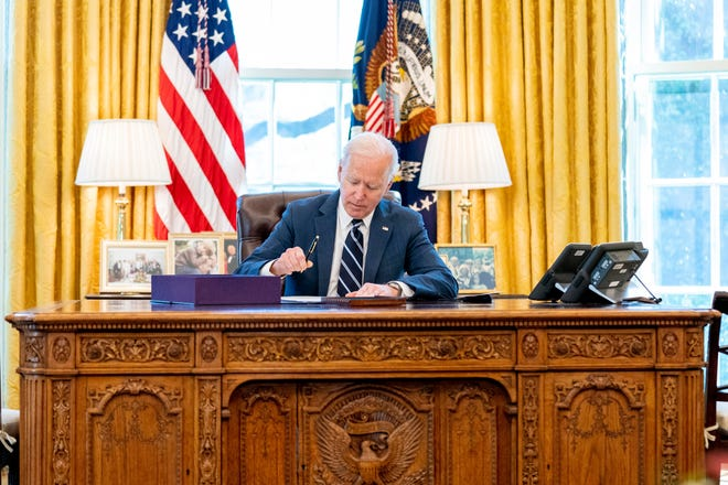 President Joe Biden signs the American Rescue Plan on Thursday at the White House.
