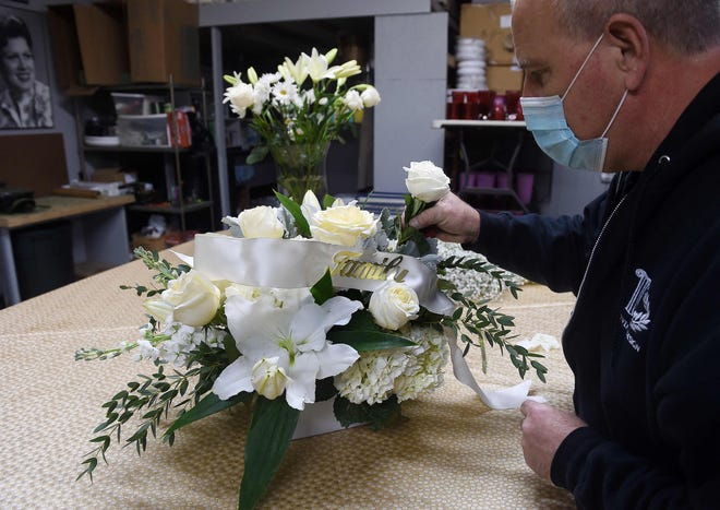 A florist demonstrates how to make floral arrangement for a funeral, amid the Coronavirus pandemic at a floral shop in Arlington, Virginia on February 22, 2021.