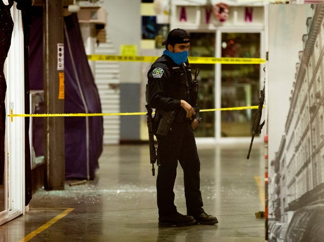 An Austin police officer works at the scene of a shooting at Marketplace Austin on North Lamar Boulevard on Friday.