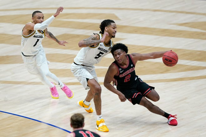 Georgia's Sahvir Wheeler (2) tries to get past Missouri's Mitchell Smith (5) and Xavier Pinson (1) in the first half of a college basketball game in the Southeastern Conference Tournament Thursday, March 11, 2021, in Nashville, Tenn. (AP Photo/Mark Humphrey)