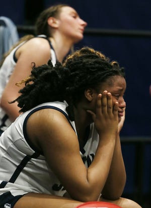 Archbishop Hoban's Adrena Gordon and Karli Anker watch the final seconds of the Knights' 55-41 loss to Newark in a Division I state semifinal at the University of Dayton Arena on Friday. [Mike Cardew/Beacon Journal]