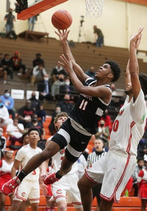 Buchtel's Marcel Boyce, Jr. puts up a shot against Toledo Central Catholic in the Griffins' 68-51 win in a Division II regional semifinal Thursday night in Elida. [Mike Cardew/Beacon Journal]
