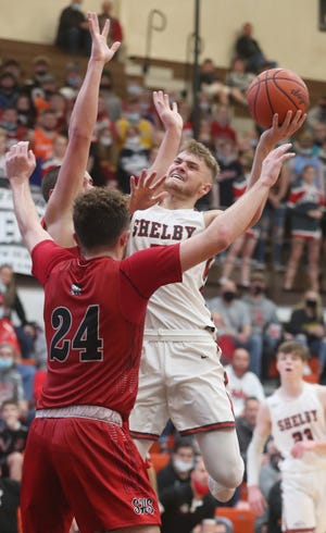 Shelby's TJ Pugh shoots over Lima Shawnee's Caden Vermillion in the second half of the  Division II regional semifinal boys basketball game at Elida High School on Thursday March 11, 2021 in Elida, Ohio. Lima Shawnee defeated Shelby 76 to 67.