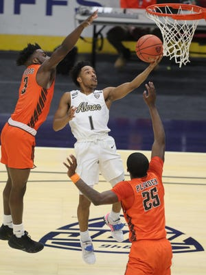 University of Akron's Loren Cristian Jackson drives between Bowling Green's Caleb Fields, left, and Daequwon Plowden for a first half basket on Thursday, March 11, 2021 in Cleveland, Ohio, in a Mid-American Conference quarterfinal game at Rocket Mortgage Fieldhouse. [Phil Masturzo/ Beacon Journal]