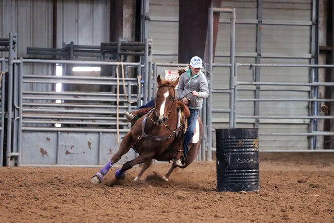 Stoney Decker makes a turn around a barrel as she attends the Kristin Weaver-Brown Barrel Racing Clinic at the Arena of Life Church.