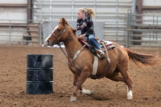 Kylee Peters makes her first turn around a barrel as she attends the Kristin Weaver-Brown Barrel Racing Clinic at the Arena of Life Church.