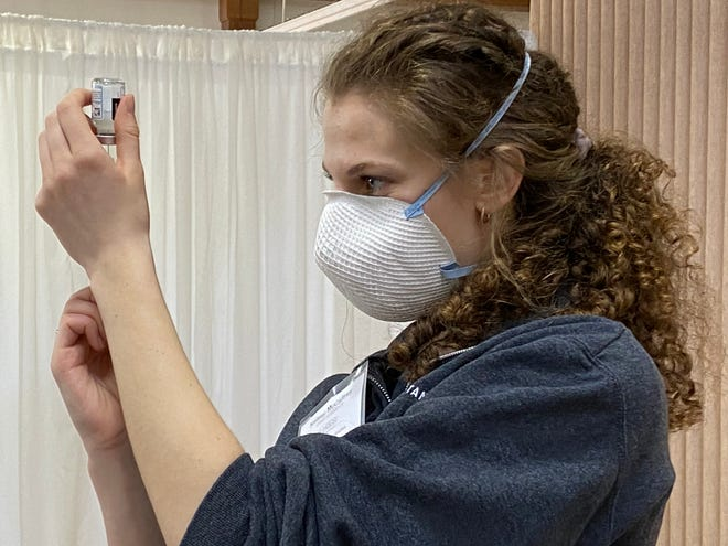 One of the students in Mount Union's physician assistant program prepares a vial of COVID-19 vaccine.