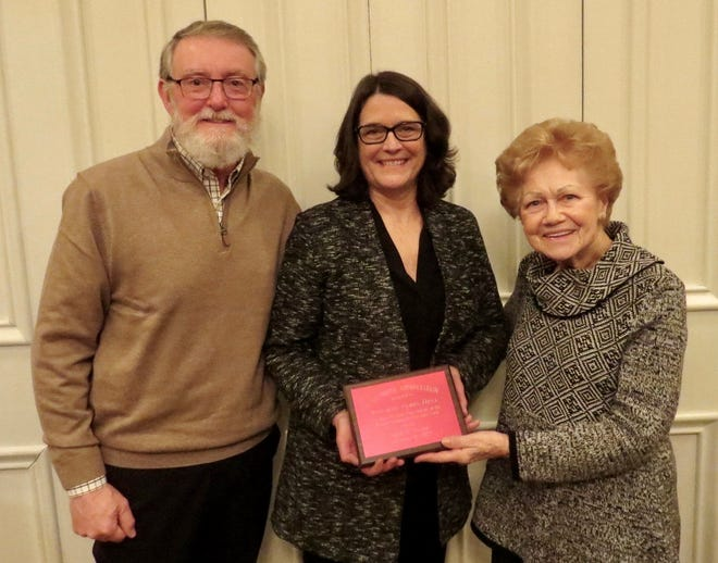 Pat Miller, right, presents a plaque to Jim and Ann Hull to thank them for a donation to Minerva Community Charitable Fund. Pictured are, from left, Jim Hull, Ann Hull and Miller.