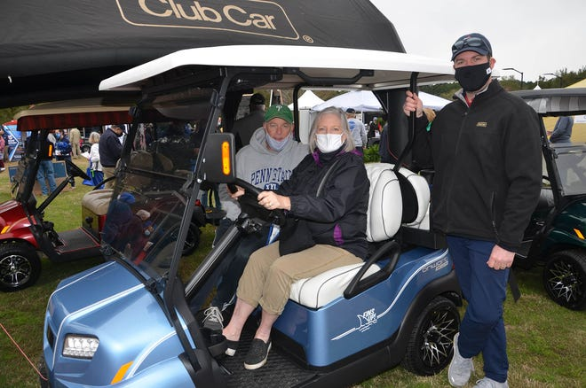 Residents sit behind the wheel of a golf cart during the recent Home and Garden Expo.