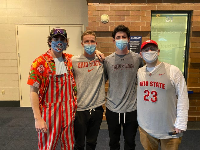 L-R: Ohio State students Cole Rapp, Davis Deasy, Dylan Meehan and Max Alter pose at Lucas Oil Stadium. Ohio State played Minnesota on Thursday, March 11, 2021, in the first game with fans in attendance this season.
