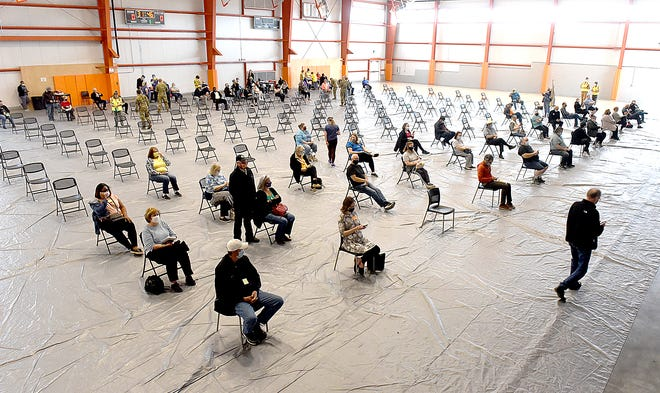 People wait before and after receiving their first COVID-19 vaccination on Friday at the Boone County mass vaccination clinic held at the Columbia Sports Fieldhouse at A. Perry Phillips Park. About 2,300 vaccine doses were available.