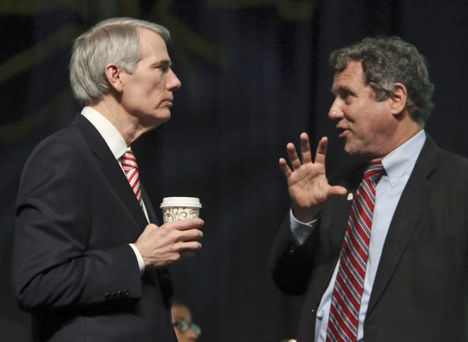 Republican Sen. Rob Portman and Democratic Sen. Sherrod Brown talk before a 2015 event at the Columbus Convention Center. The Ohioans differ sharply on the newly signed $1.9 trillion COVID relief bill.