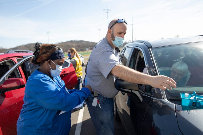 Rick Lanuzza, a paramedic with the Fredricktown Fire Department, leans into a car to talk to a patient receiving their second vaccination while LPN De'Jah Bennett takes notes at the drive-up vaccination area Friday in Mount Vernon, Ohio.