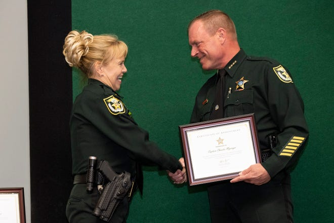 Officer Christie Mysinger is promoted to Captain by Sheriff Peyton Grinnell at the Lake County Sheriff's Office promotion ceremony on Wednesday. [Cindy Peterson/Correspondent]