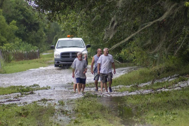 Workers with the Terrebonne Levee District, along with residents, respond after Hurricane Barry's storm surge overtopped a flood-protection levee in Montegut on July 13, 2019.