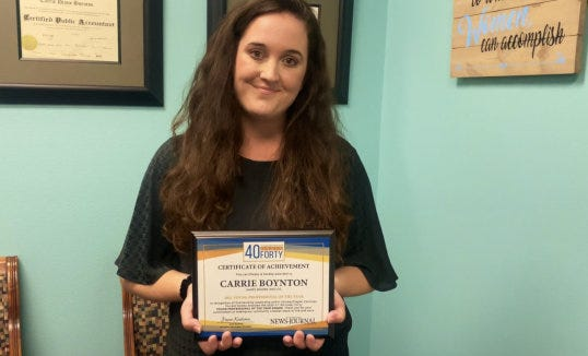 """Carrie Boynton, tax director at James Moore & Co. CPAs & Consultants in Daytona Beach, holds the Volusia-Flagler area """"2021 Young Professional of the Year"""" award she recently received from The Daytona Beach News-Journal. Kaitlyn Stier, News-Journal marketing event manager, surprised Boynton by presenting her with the award at her office."""