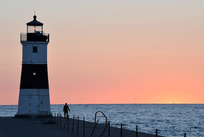 Just before sunrise July 19, 2016, a fisherman works his line near the North Pier marker light at Presque Isle State Park.