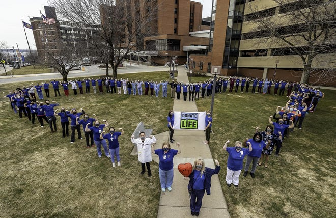 UPMC Hamot employees gathered on the Erie hospital's lawn Wednesday to pose and honor Carl Seon, M.D., a Hamot physician who recently underwent a double-lung transplant after battling COVID-19.