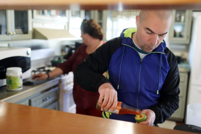 Andy Osterberg, a resident in a home operated by the Mediapolis Care Facility, makes a shake in the kitchen March 11 at 312 North St. in Mediapolis.