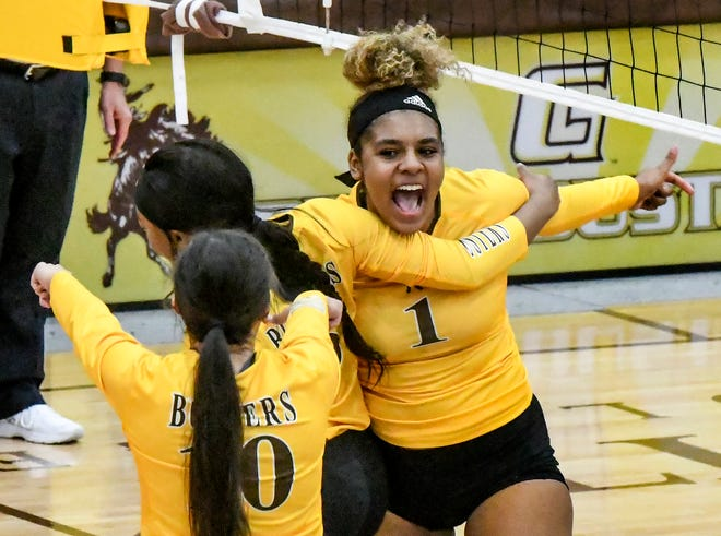 Garden City Community College's Tauja Durham, right, celebrates making a kill for a point Thursday with teammates Angel Sherman and Remi Vargas, left, during a match against Independence at Perryman Athletic Complex.