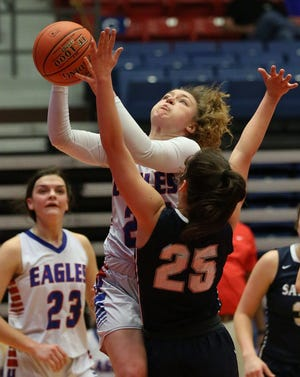 Hugoton's Mikyn Hamlin (25) drives to the basket over Sabetha's Melinna Schumann (25) during their KSHSAA Class 3A State semi-final game at the Sports Arena Thursday. Sabetha defeated Hugoton 57-55.