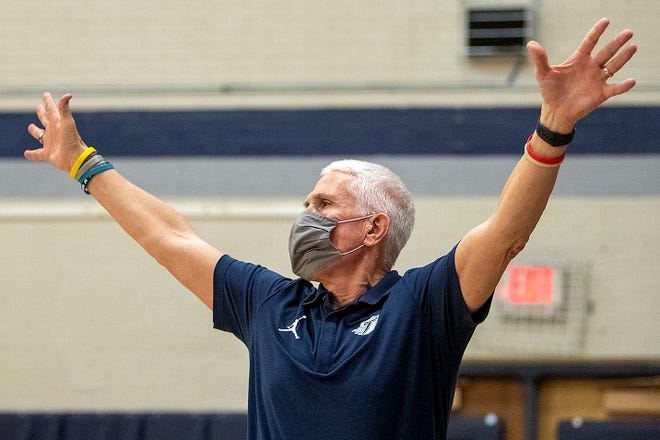 """Monmouth-Roseville boys basketball coach Chuck Grant encourages his defense from the sideline of the Titans' 49-40 season-ending loss to Macomb on Thursday, at """"The Shoebox."""" The game was the last in Grant's 28-year career."""