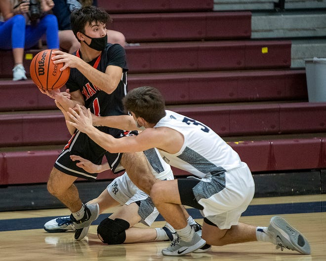 Macomb's Connor Watson looks for an open teammate as a pair of Monmouth-Roseville players defend during the Bombers' 49-40 win over the host Titans' on Thursday, in Monmouth.