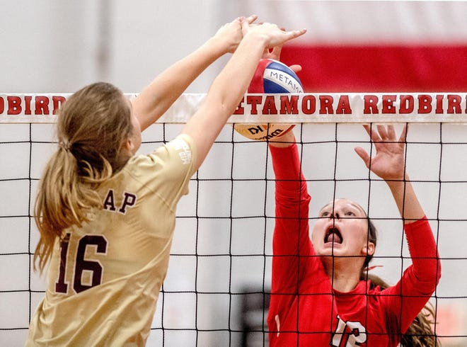 Metamora's Hannah Tellor (12) battles Dunlap's Emma Robben at the net during their match in 2019 in Metamora.