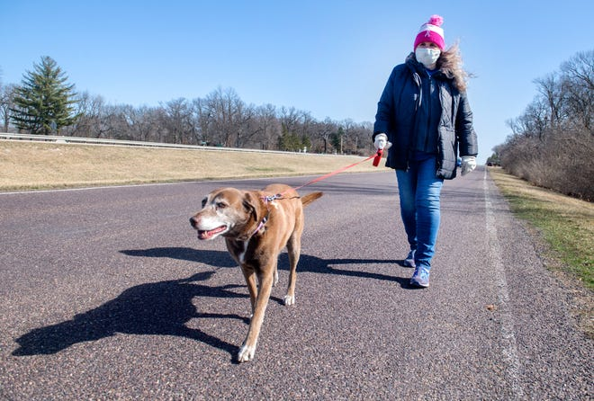 Suzie Gorman Pierce, 77, walks her dog Coco along Old Germantown Road near her home in Germantown Hills. Pierce had nearly no contact with others besides the 11-year-old Lab-mix during the deadliest days of the pandemic, depending on her faith to stave off extreme feelings of loneliness.