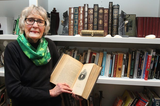 Mickey Martin holds a history book about Freeport from 1880 that she keeps in her library on Thursday, March 11, 2021, at her home in Freeport. Martin will be honored by the City Council on Monday for her years of community service.