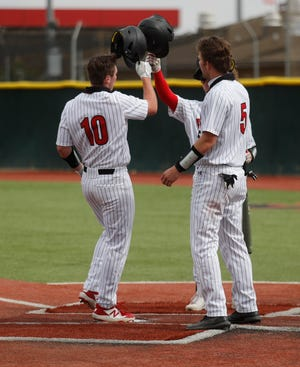 Lubbock Cooper's Cutter Douglas (10) celebrates with teammates at home after hitting a two-run home run in the 5th inning of a nondistrict game Friday Mar. 12,  2021 against San Angelo Central as part of the First Bank Classic at First United Park in Woodrow, Texas. [Mark Rogers/For A-J Media]