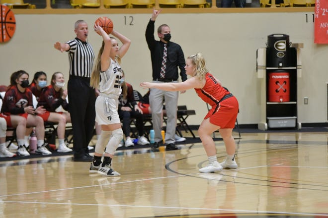 St. Thomas Aquinas' Madison Skelton (32) looks for an open teammate while being defended by Lansing's Caitlin Bishop (11) during Thursday's Class 5A semifinal at White Auditorium in Emporia.