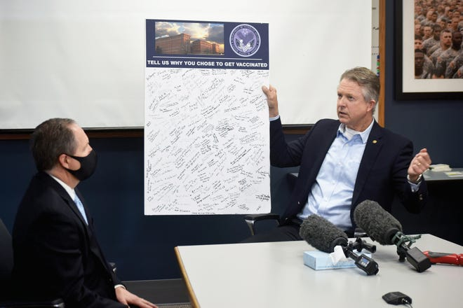U.S. Sen. Roger Marshall, right, holds a display of handwritten messages from veterans regarding why they have received COVID-19 vaccines. Marshall visited the Eisenhower VA Medical Center on Friday. Also pictured is Rudy Klopfer, director and CEO of the VA Eastern Kansas Health Care System.