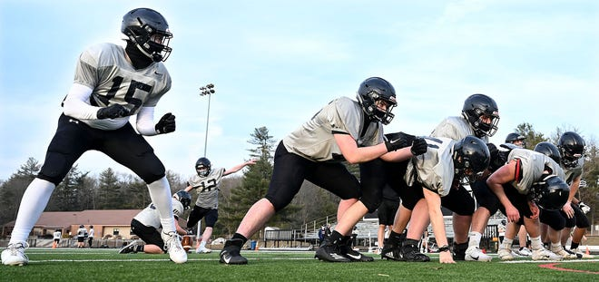 Blockers line up as Bellingham's Sean Edwards (12) practices kicking field goals during the Blackhawks' football practice at Bellingham High School on March 11, 2021.