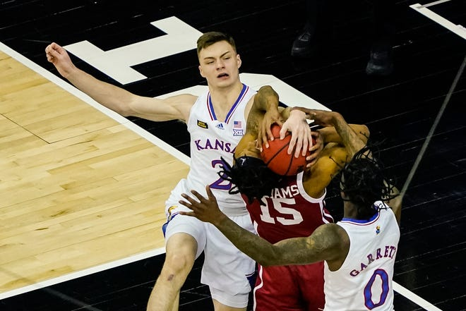 Kansas guard Christian Braun (2) blocks the shot of Oklahoma guard Alondes Williams (15) during the first half of a Big 12 quarterfinal Thursday in Kansas City, Mo.